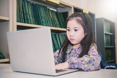 Liten asiatisk flicka med bärbara datorn som spelar dataspelar Fotografering för Bildbyråer