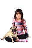Liten asiatisk flicka med hennes lilla mops Royaltyfri Bild