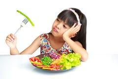 Liten asiatisk flicka med uttryck av avsmak mot broccoli Arkivbilder