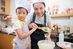 Liten asiatisk flicka- och moderdanandepannkaka Royaltyfri Bild