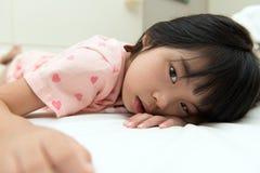 Liten asiatisk flicka på säng Royaltyfri Bild