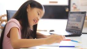 Liten asiatisk flicka som drar en bild på tabellen arkivfilmer