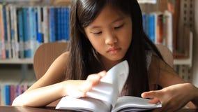 Liten asiatisk flicka som läser en bok lager videofilmer