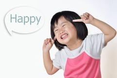 Liten asiatisk flicka som ler och pekar till hennes framsida arkivfoto
