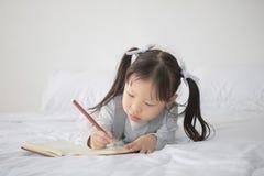 Liten asiatisk flicka som ligger på säng och skriver alfabet på anteckningsboken Arkivbilder