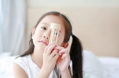 Liten asiatisk flicka som rymmer sandglass i hand med att se till och med kamera Väntetider med timglas arkivfoton