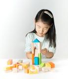 Liten asiatisk flicka som spelar färgrika träsnitt Royaltyfria Foton
