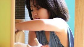 Liten asiatisk flicka som spelar med dockan arkivfilmer