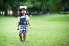 Liten asiatisk flicka som spelar på grönt gräs på parkera Arkivfoto
