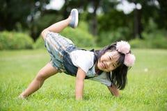 Liten asiatisk flicka som spelar på grönt gräs på parkera Royaltyfri Fotografi