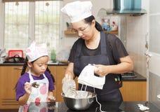 Liten asiatisk flickor och moderdanandesockerkaka Fotografering för Bildbyråer