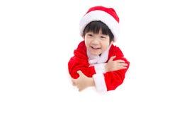 Liten asiatisk pojke i den Santa Claus likformign med ett tomt baner Arkivfoton