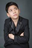 Liten asiatisk pojke i svart dräktrubbning, fördjupningsframsida Arkivfoton