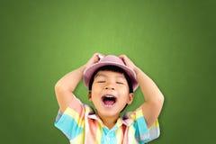 Liten asiatisk pojke med ett hattskri på grönt bräde Fotografering för Bildbyråer