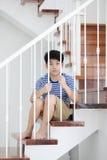 Liten asiatisk pojke som är borttappad i tankar och som är ledsen arkivfoton