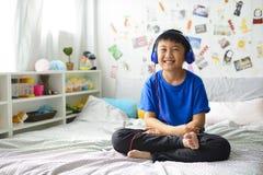 Liten asiatisk pojke som använder hörlurar, och le som är lyckligt medan lyssnande musik på säng fotografering för bildbyråer