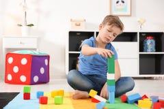 Liten autistisk pojke som spelar med kuber arkivfoto