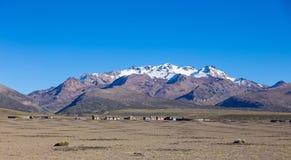 Liten by av herdar av lamor i de Andean bergen  fotografering för bildbyråer