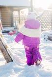 Liten babeflicka som spelar på vinterlekplatsen Arkivfoton