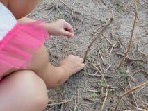 Liten babys händer som spelar och trycker på torra gräs, jord och unga spiragräs arkivbild