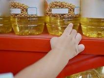 Liten babys hand som tar en flaska av matolja på för att bordlägga royaltyfri foto