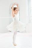 Liten ballerinaflicka i en ballerinakjol Förtjusande barn som dansar klassisk balett i en vit studio arkivbilder