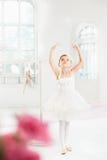 Liten ballerinaflicka i en ballerinakjol Förtjusande barn som dansar klassisk balett i en vit studio Fotografering för Bildbyråer