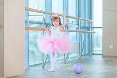 Liten ballerinaflicka i en rosa ballerinakjol Förtjusande barn som dansar klassisk balett i en vit studio Barndans ungar Royaltyfria Foton
