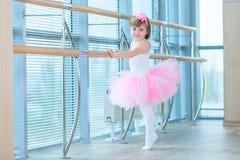 Liten ballerinaflicka i en rosa ballerinakjol Förtjusande barn som dansar klassisk balett i en vit studio Barndans ungar Royaltyfria Bilder