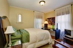 Liten beige sovruminre med ädelträgolvet och vit sängkläder för gräsplan Royaltyfria Foton