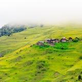 Liten bergby i morgonmist Georgia, Tusheti arkivbild