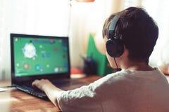 Liten beroende gamerpojke som spelar på bärbara datorn royaltyfri fotografi