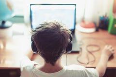 Liten beroende gamerunge som spelar på bärbara datorn royaltyfri fotografi