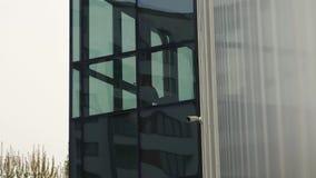 Liten bevakningkamera på kontorsbyggnaden nära stora fönster