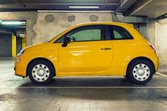 Liten bil i undergroudparkeringsgrunge Arkivbild