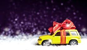 Liten bil med en dekorativ pilbåge i snö arkivbild