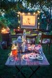 Liten bio med gamla parallella filmer i sommarträdgård Arkivbild