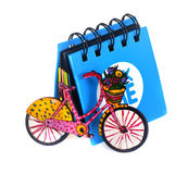 Liten blå anteckningsbok som är bredvid en liten cykel Royaltyfri Bild