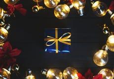 Liten blå gåva inom ljusa kulor och röd julstjärna på svart W royaltyfria foton