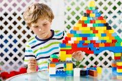 Liten blond barn- och ungepojke som spelar med massor av färgrika plast- kvarter Royaltyfria Foton