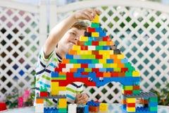 Liten blond barn- och ungepojke som spelar med massor av färgrika plast- kvarter Arkivfoton