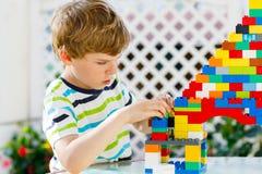 Liten blond barn- och ungepojke som spelar med massor av färgrika plast- kvarter Arkivbild