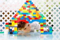 Liten blond barn- och ungepojke som spelar med massor av färgrika plast- kvarter Royaltyfri Fotografi