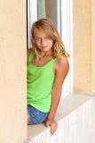 Liten blond Caucasian flicka i fönstret royaltyfri foto