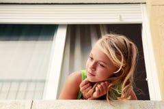 Liten blond Caucasian flicka i fönstret, utomhus- stående royaltyfria foton