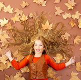 Liten blond flicka för höstfall på torkade treeleaves Royaltyfri Foto