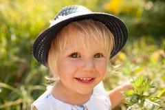 Liten blond flicka i blå hatt Arkivbild