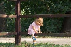 Liten blond flicka i rosa klänning som klättrar över trästaketet i sommardag på skogbakgrunden Kall i byn fotografering för bildbyråer