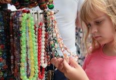 Liten blond flicka i souvenirmarknaden Fotografering för Bildbyråer
