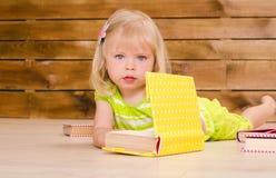Liten blond flicka med böcker inomhus royaltyfri fotografi